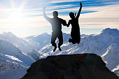 Couple Jumping Together On Mountain