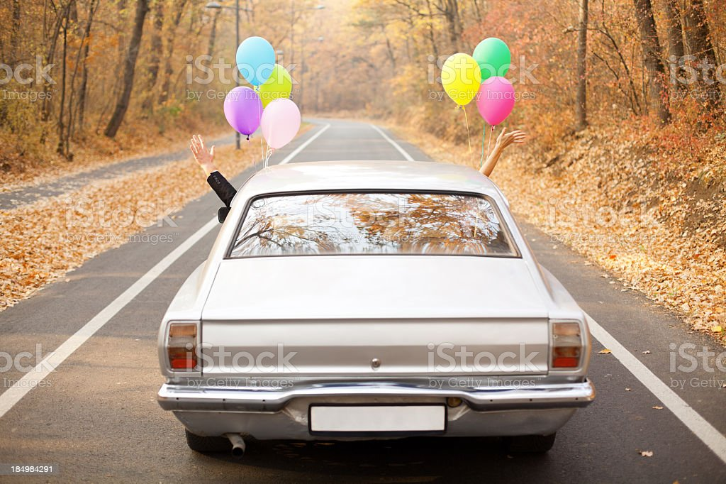A couple just married with balloons tied to their car stock photo