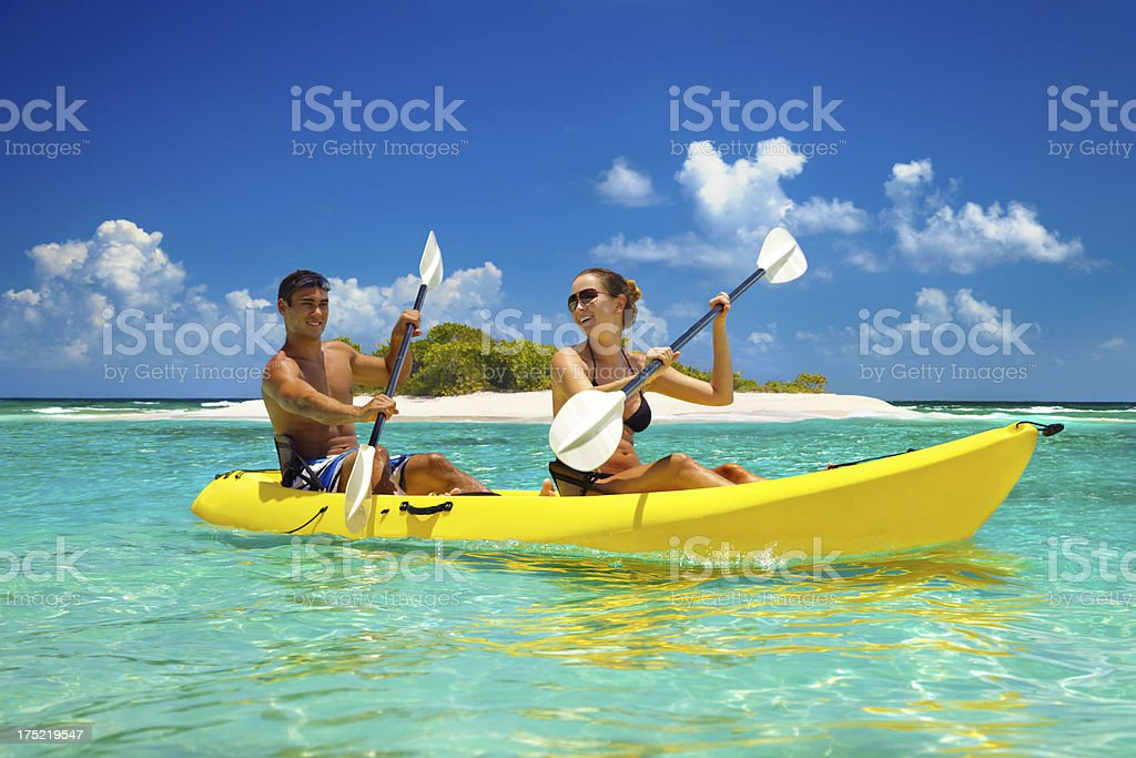 couple kayaking by a tropical island in the Caribbean stock photo