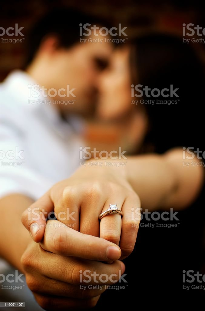 Couple kisses as they show off engagement ring stock photo