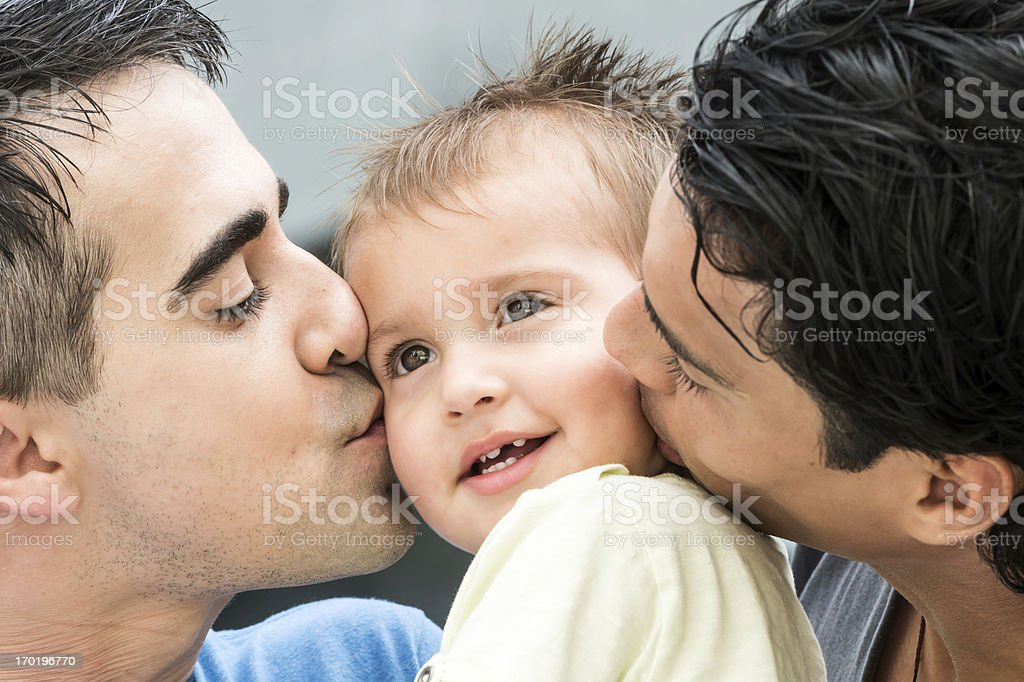 couple kisses each cheek of their child royalty-free stock photo