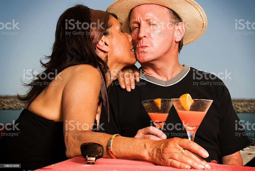 Couple Kissing and Drinking Cocktails by Sea stock photo