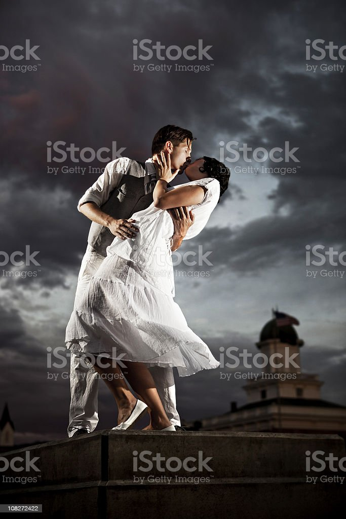 Couple kissing at dusk in front of a moody sky royalty-free stock photo