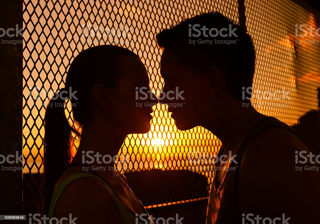 Couple kissing at sunset stock photo