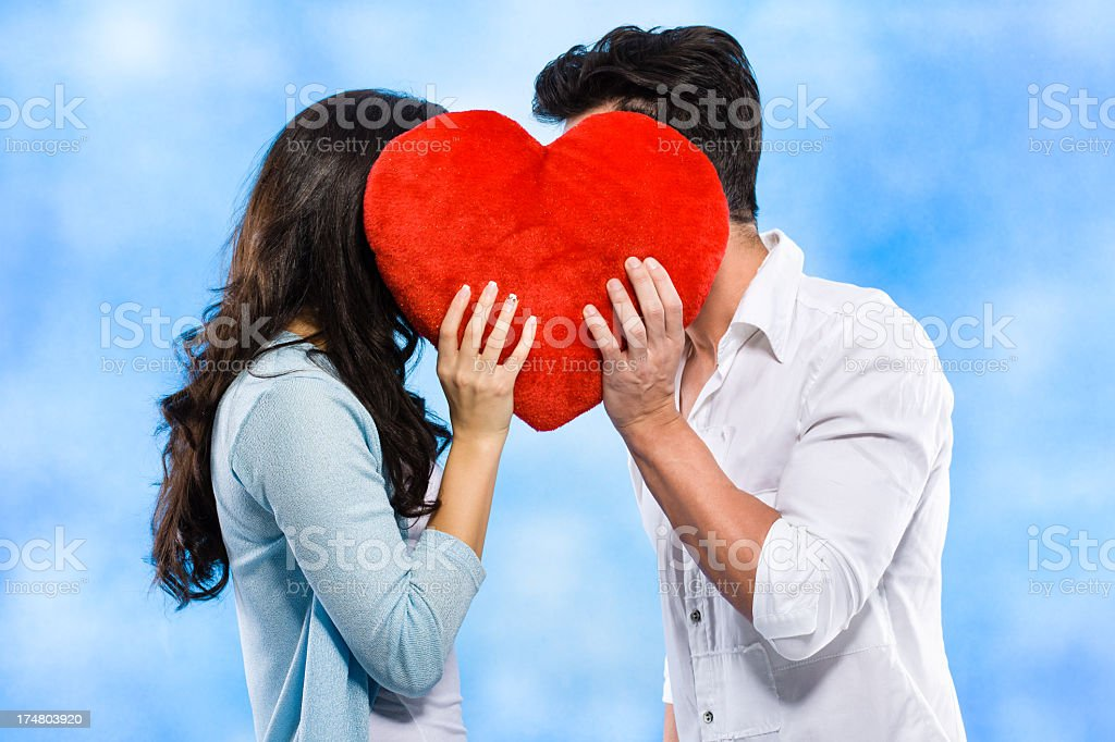 Couple kissing behind the red heart royalty-free stock photo
