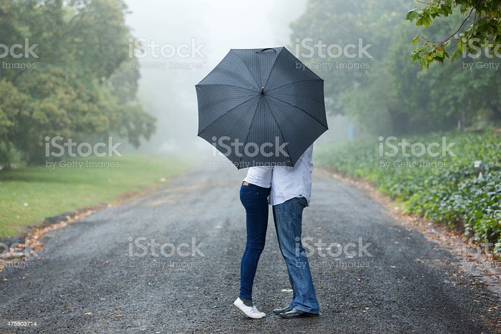 couple kissing behind the umbrella stock photo
