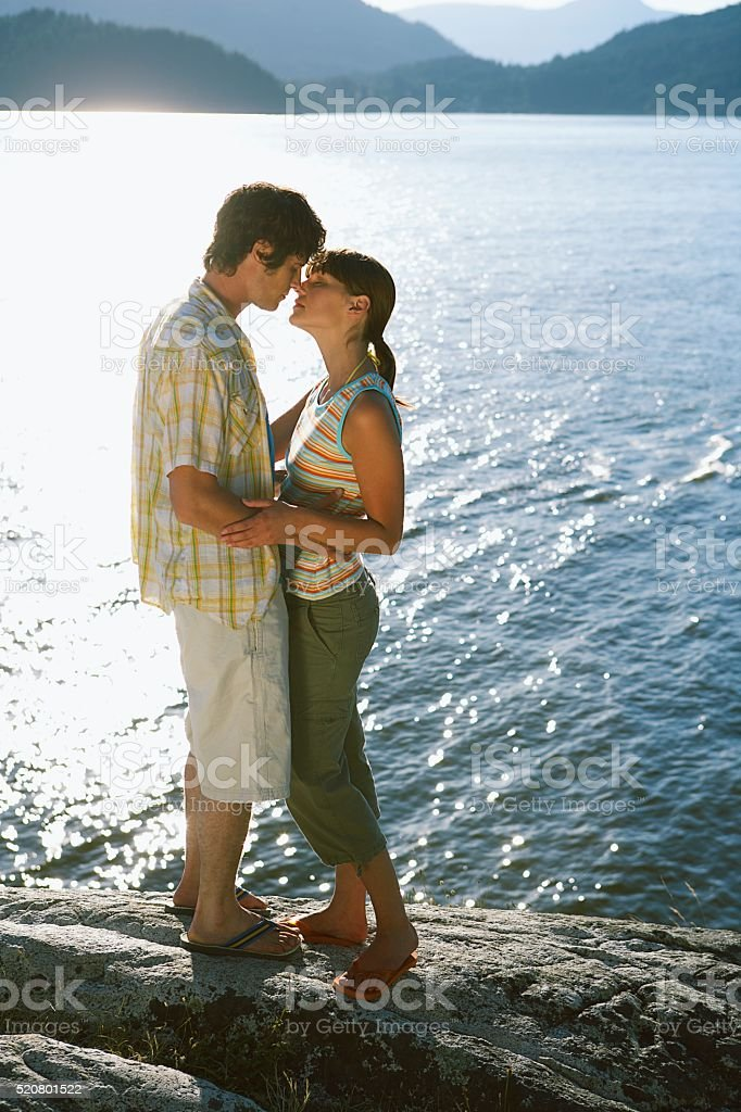 Couple kissing beside a lake stock photo