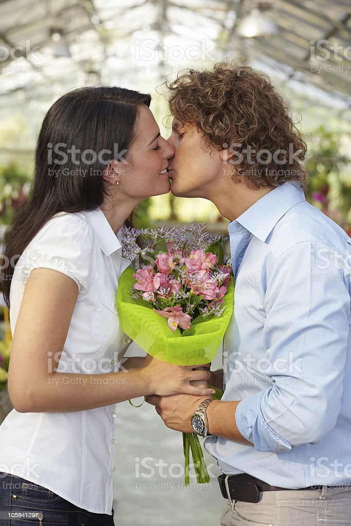 couple kissing in flower nursery royalty-free stock photo