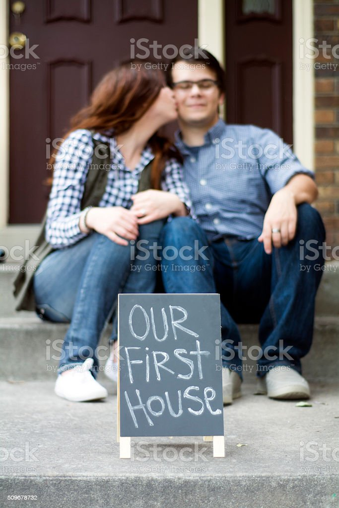 couple kissing on front steps of new home stock photo