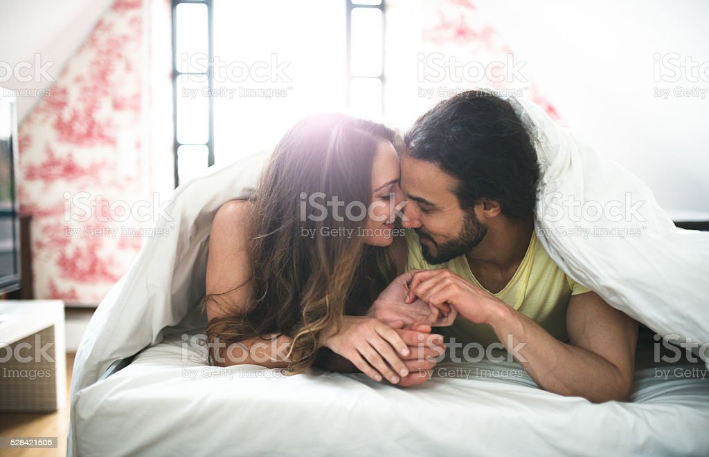 couple kissing on the bed on early morning stock photo