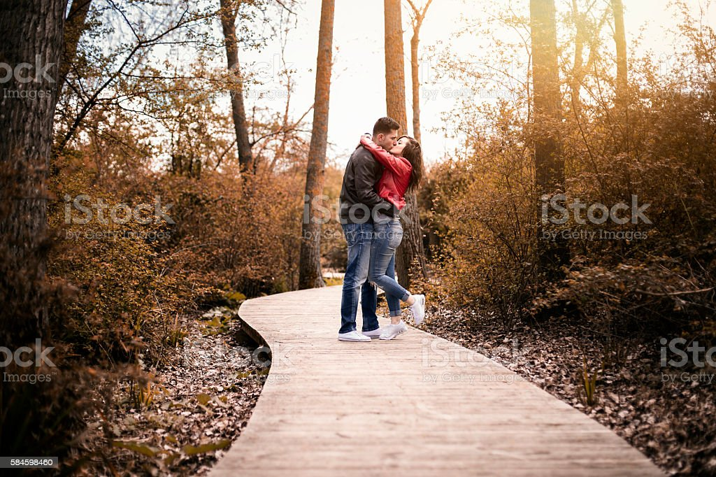 couple kissing outdoor in the park stock photo