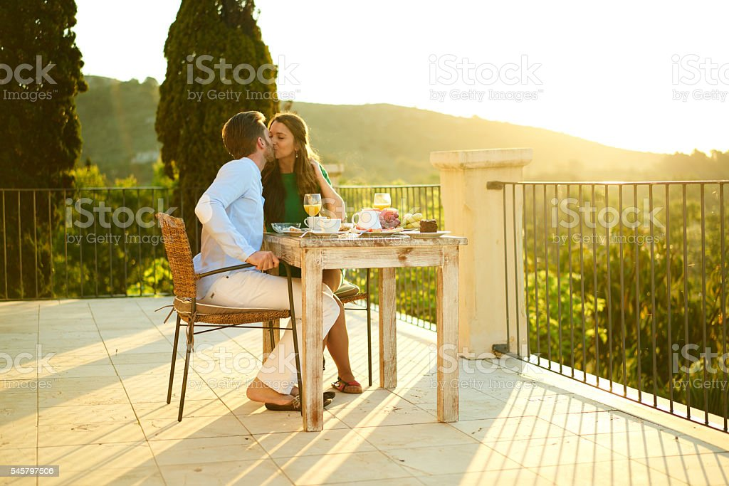 couple kissing outside at breakfast table stock photo