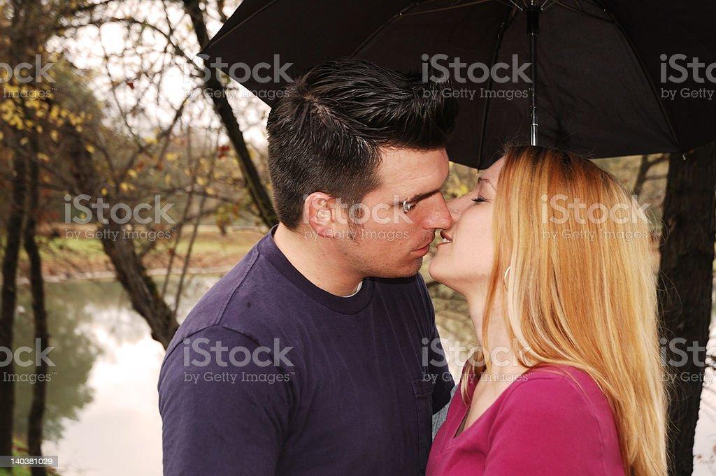 Couple Kissing Under an Umbrella stock photo