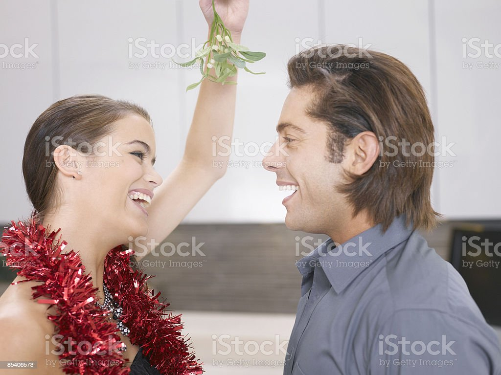 Couple kissing under mistletoe royalty-free stock photo