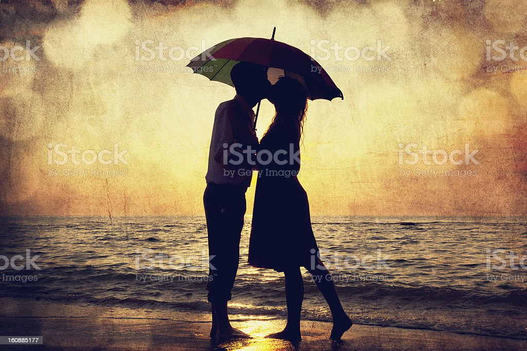 Couple kissing under umbrella at the beach in sunset. stock photo