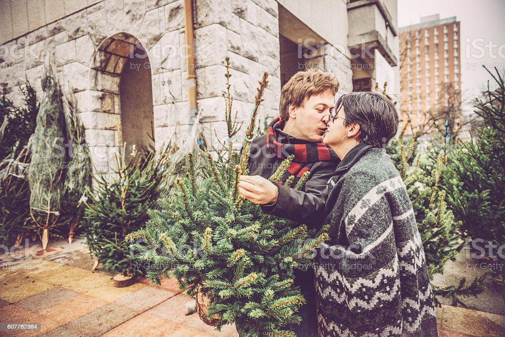 Couple Kissing while Choosing Christmas Tree, City Market, Europe stock photo