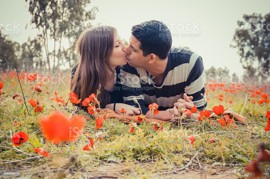 Couple kissing while lying in a field of red poppies stock photo