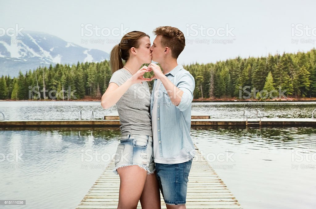 Couple kissing with each other at the lake stock photo