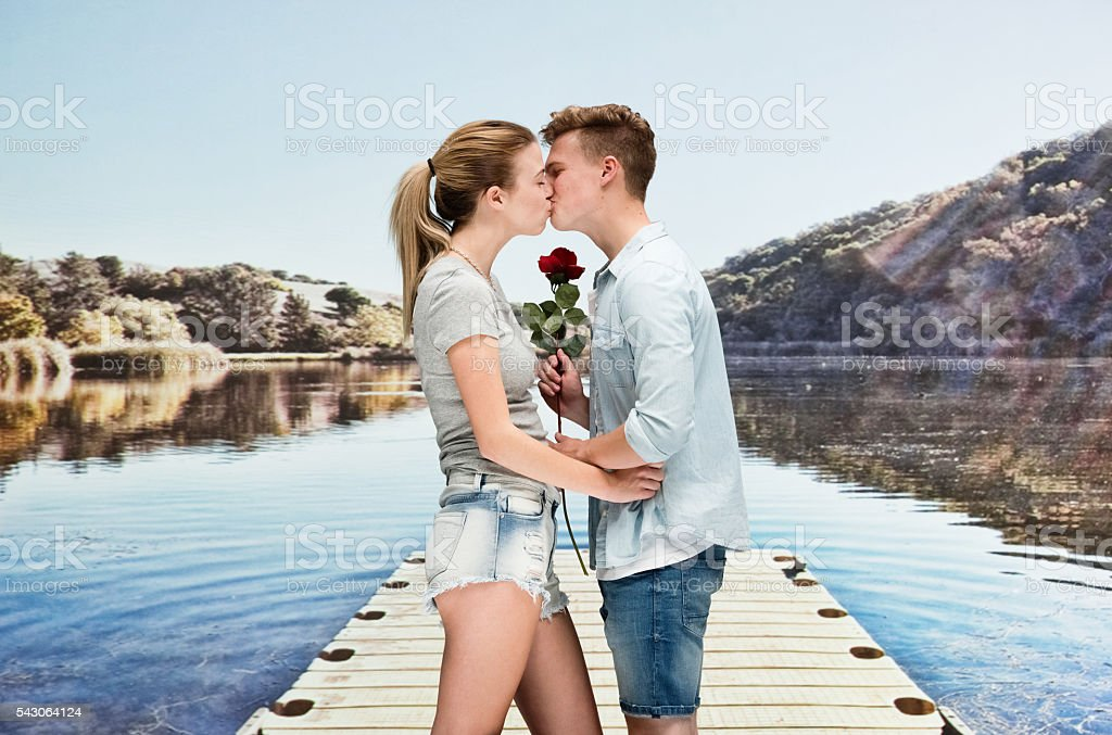 Couple kissing with each other in front of lake stock photo