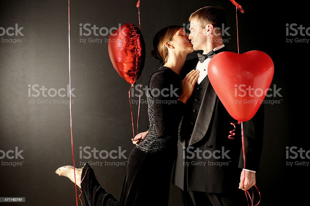 Couple kissing with heart shaped balloons royalty-free stock photo