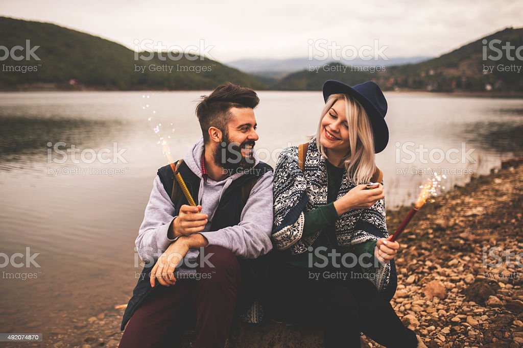 Couple laughing and holding Christmas sparklers. stock photo