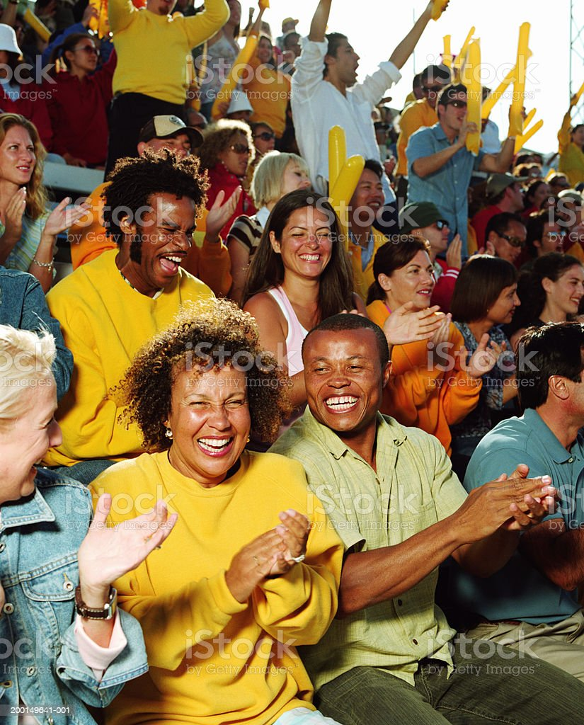 Couple laughing, cheering with crowd in stadium stock photo