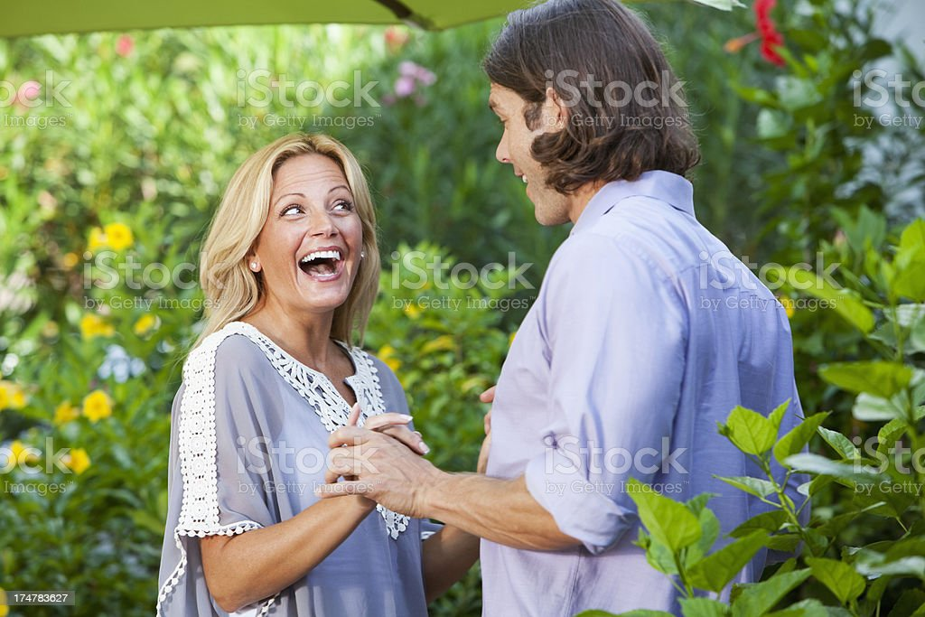 Couple laughing in garden stock photo