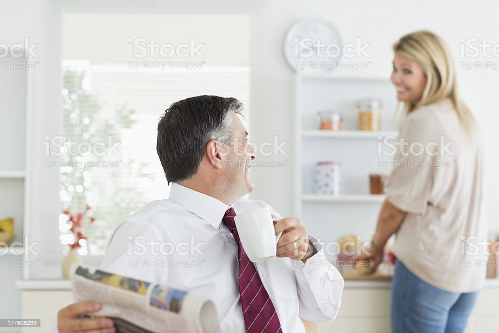 Couple laughing together in kitchen before work royalty-free stock photo