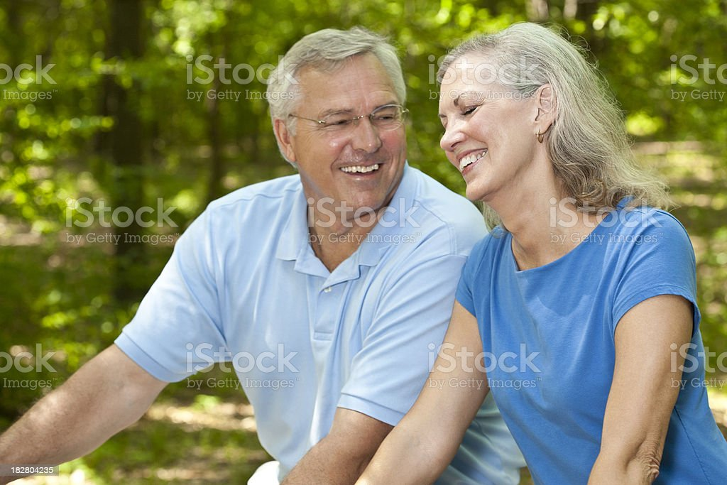 Couple Laughing Together While Biking Through the Woods royalty-free stock photo