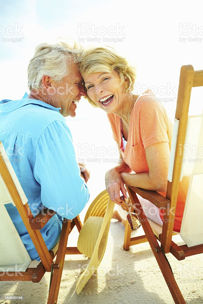 Couple laughing while enjoying the beach stock photo