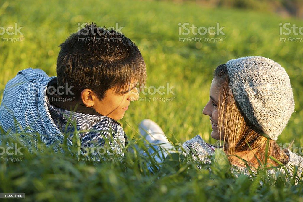 Couple en champ main dans l'herbe au coucher du soleil. photo libre de droits