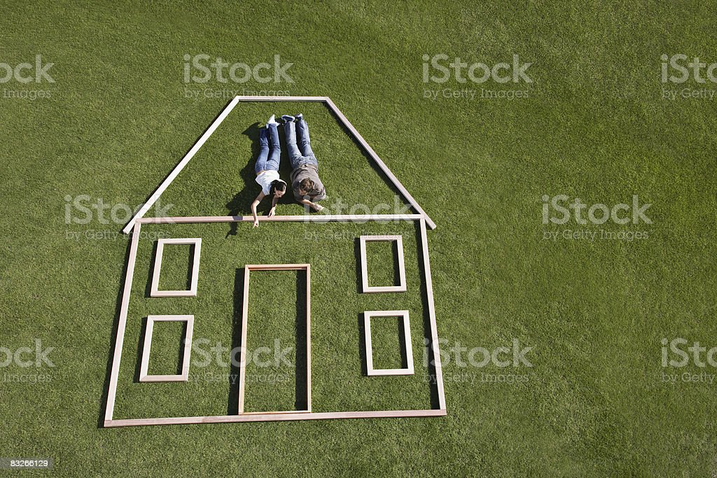 Couple laying inside house outline royalty-free stock photo