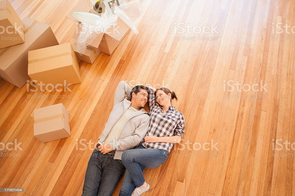 Couple laying on floor of new house stock photo