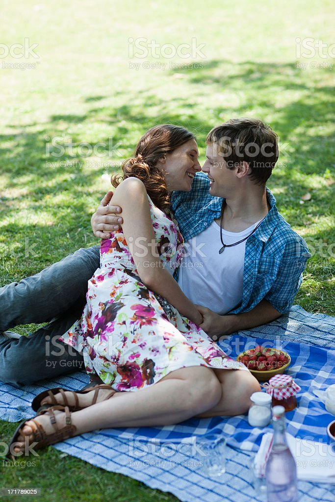 Couple laying together in grass and having picnic stock photo