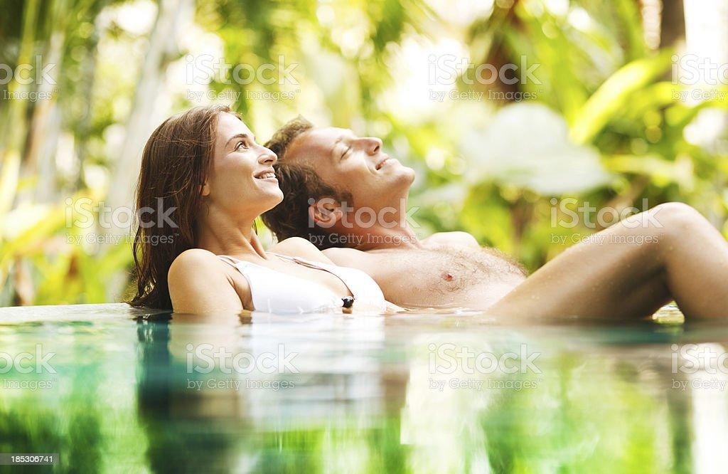 Couple leaned on the edge of a tropical pool. stock photo