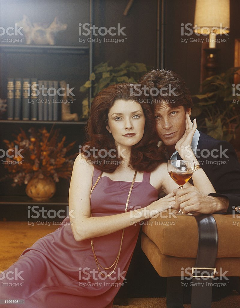 Couple leaning on sofa, woman holding glass royalty-free stock photo
