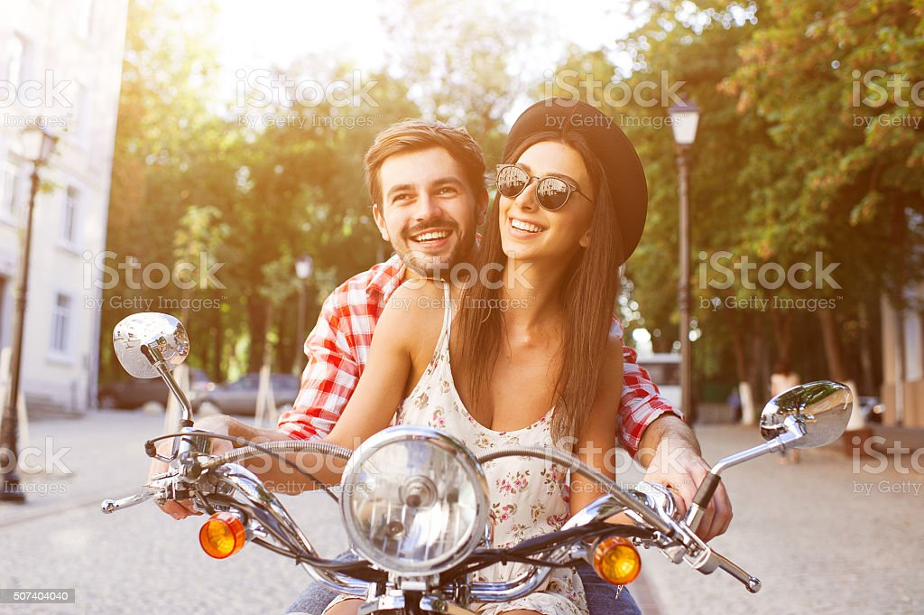 Couple learning to drive a scooter on road stock photo