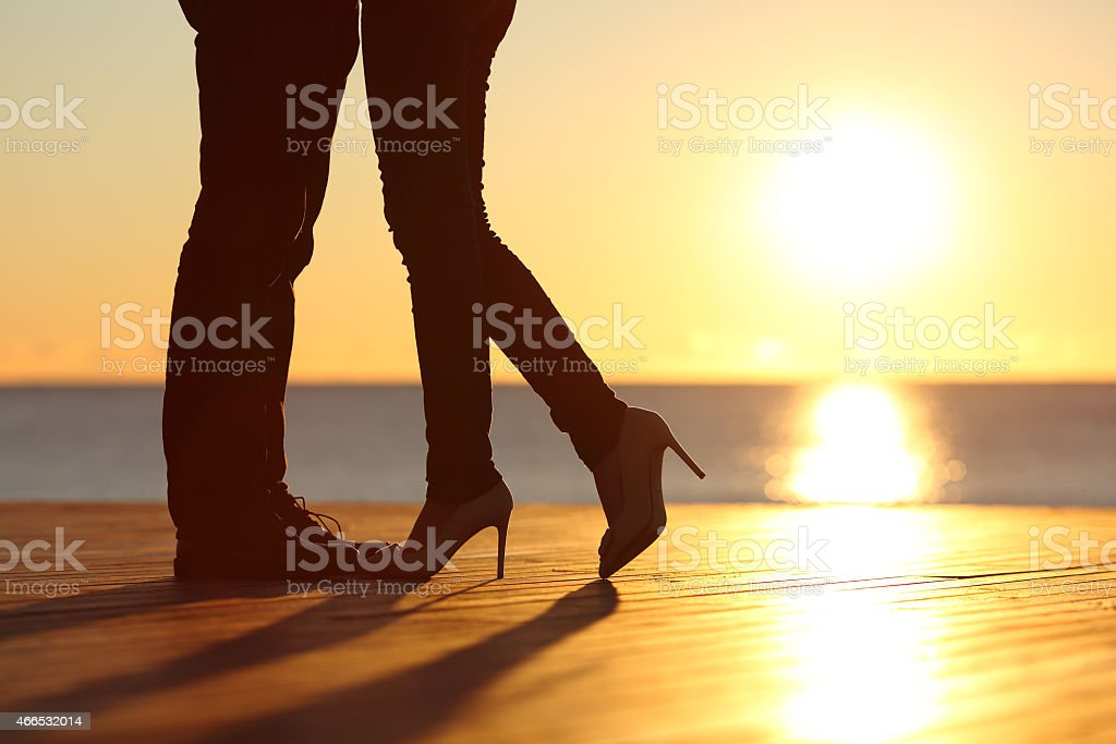 Couple legs falling in love hugging at sunset stock photo