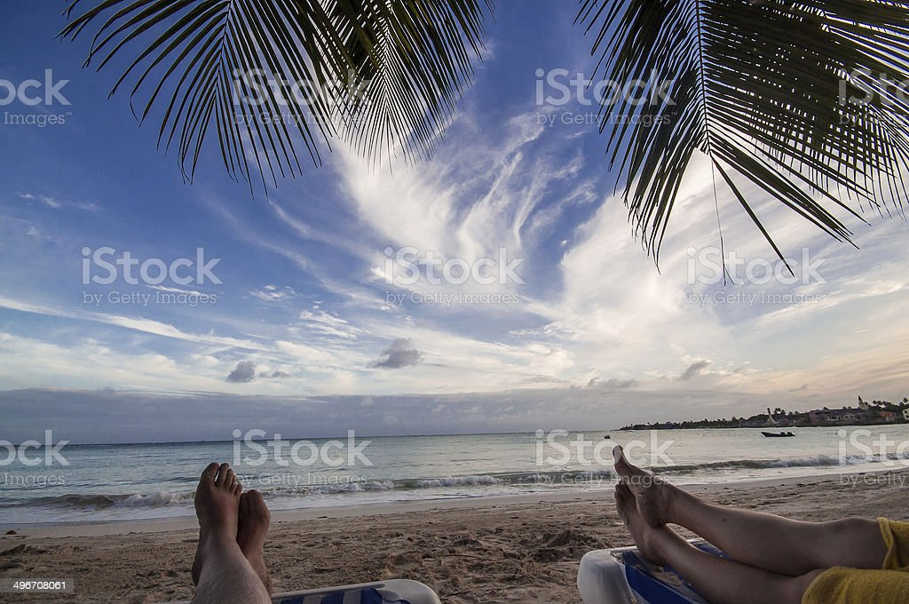 Couple legs on the evening tropical beach stock photo