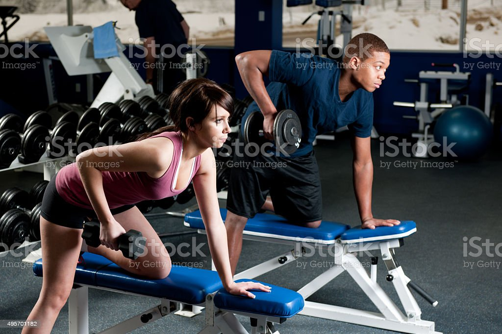 Couple Lifting Weights at the Gym stock photo