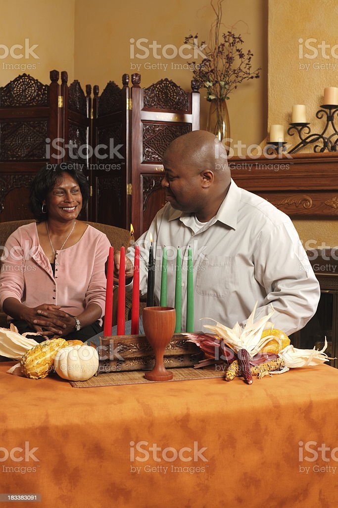 Couple lighting Kwanzaa candles stock photo