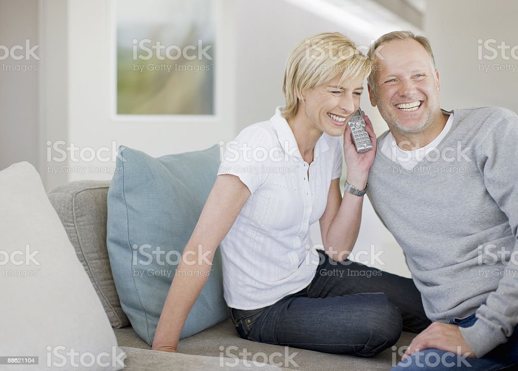 Couple listening to cordless phone together stock photo