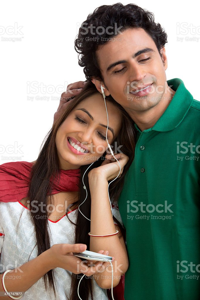 Couple listening to music on a mobile phone and smiling royalty-free stock photo