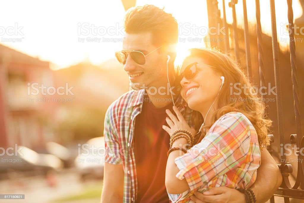 Couple listening to music on mobile device stock photo