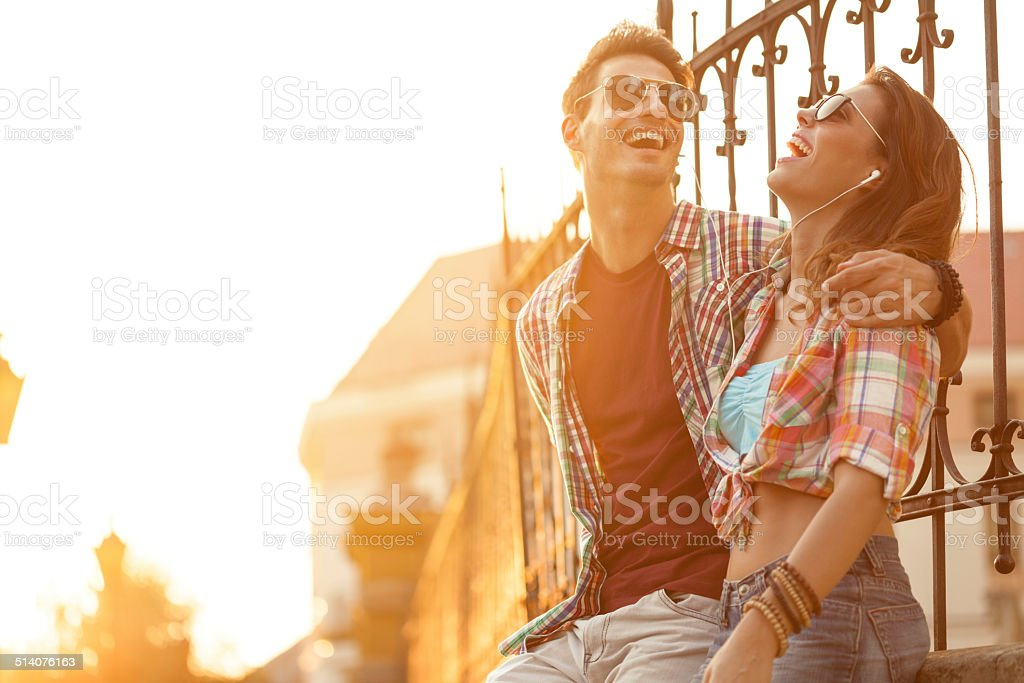 Couple listening to music on mobile phone together stock photo
