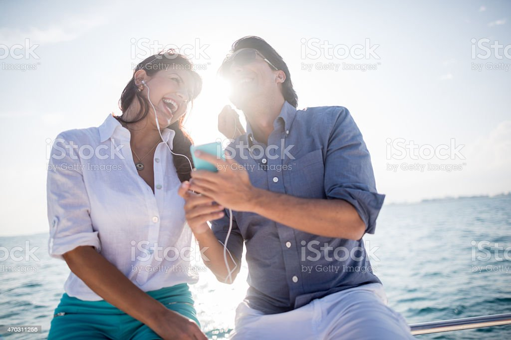 Couple listening to music while sailing stock photo