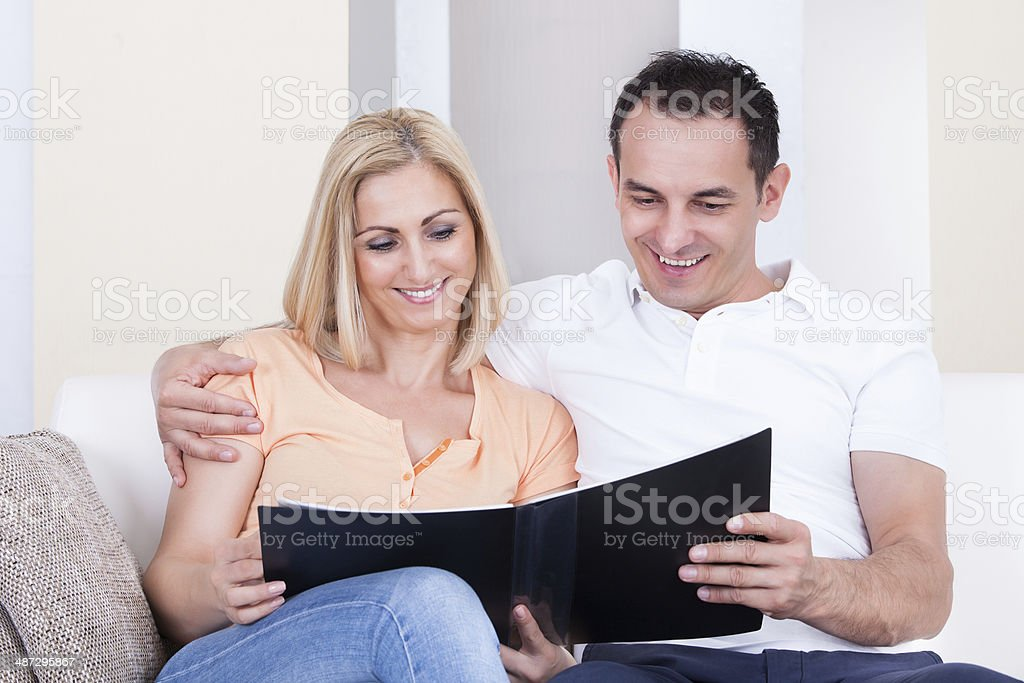 Couple Looking At Album stock photo