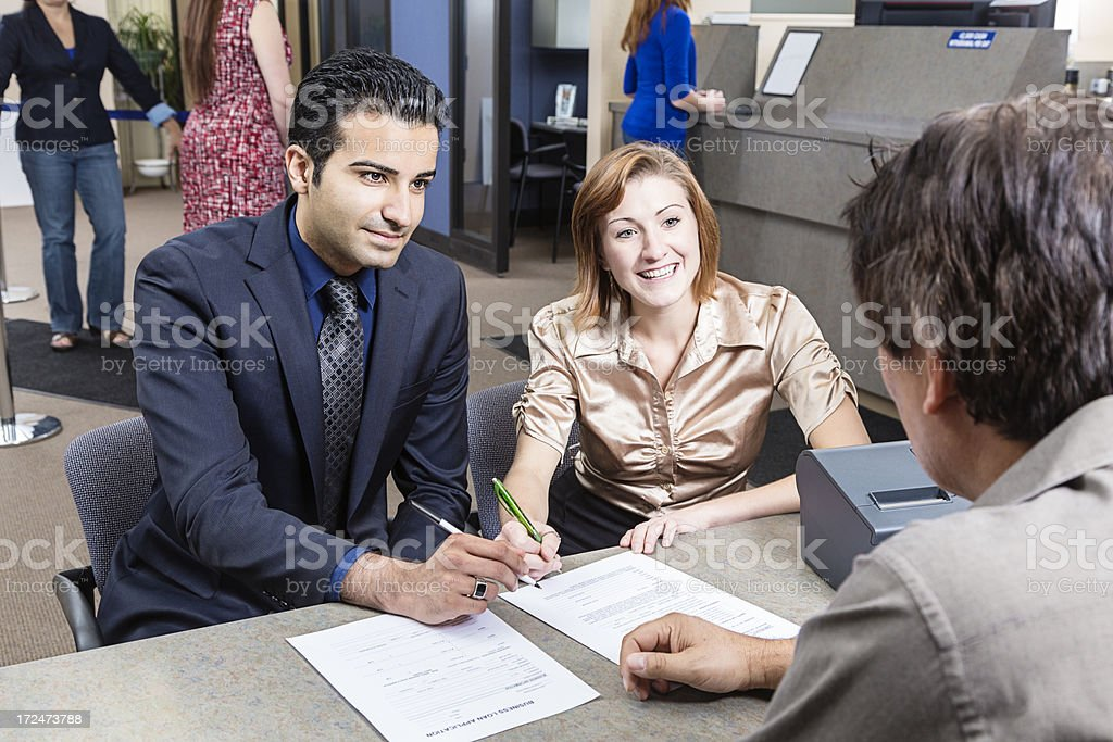 Couple Looking at Application With Banker royalty-free stock photo