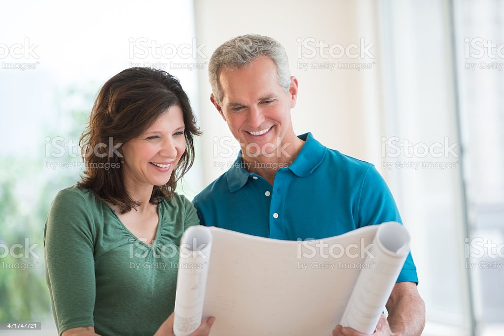 Couple Looking At Blueprint In New House stock photo