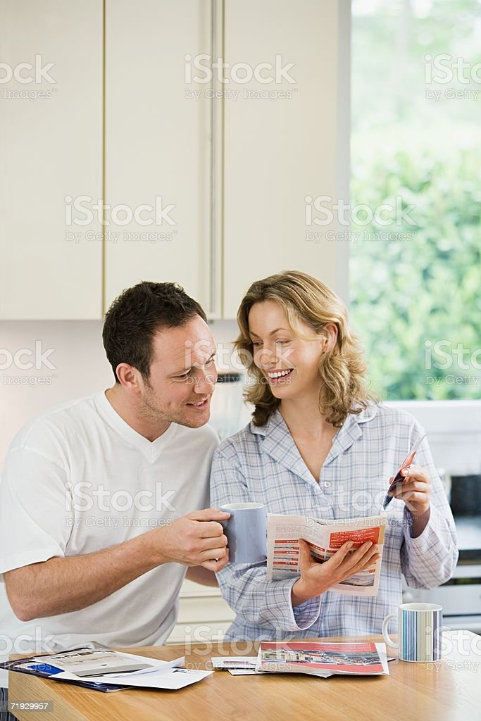 Couple looking at brochure in kitchen royalty-free stock photo